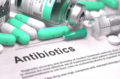 Antibiotics. Medical Report with Composition of Medicaments - LIght Green Pills, Injections and Syringe. Blurred Background with Selective Focus.