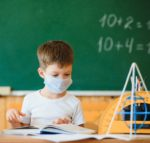 Schoolboy in the classroom in a protective mask. The concept of schooling during the epidemic